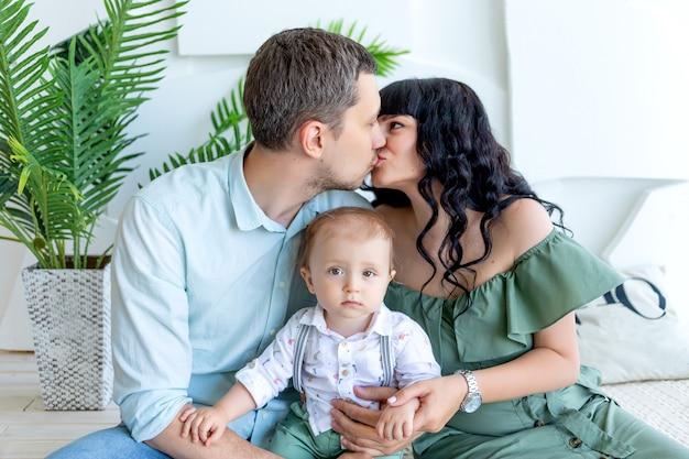 ママとパパのキス、腕の中で赤ちゃんl、幸せな家族の概念、家族の日