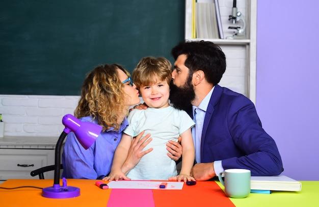Мама и папа целуют своего сына, симпатичного ученика, и его родители впервые в школе делают учебу