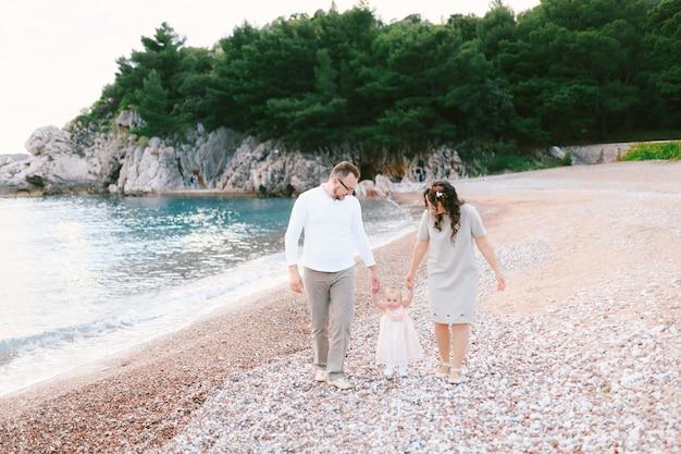 엄마와 아빠는 빌라 마일로세르 스베티 스테판 섬 근처 해변을 따라 손으로 어린 소녀를 이끌고 있습니다.