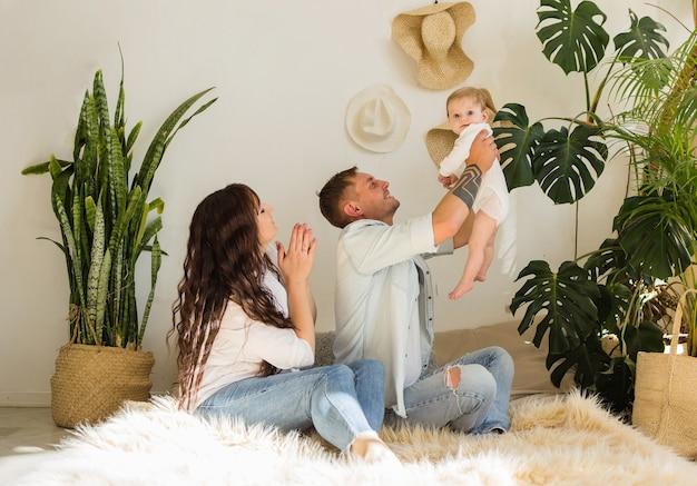 ママとパパはベッドの上の部屋で女の赤ちゃんと遊ぶ