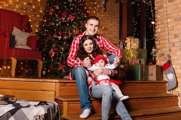 엄마와 아빠가 장식 된 크리스마스 스튜디오에서 매력적인 작은 딸과 함께 포즈를 취합니다. 새해 사진 세션.