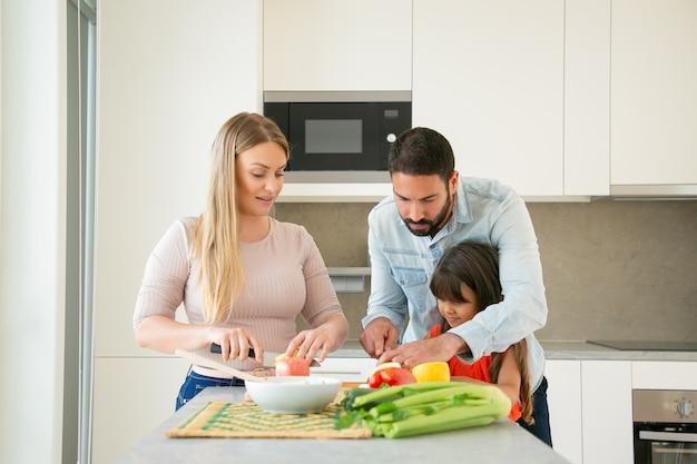 ママとパパが子供に料理を教える。若いカップルと彼らの女の子が台所のテーブルでサラダの新鮮な果物と野菜をカットします。健康的な栄養やライフスタイルのコンセプト