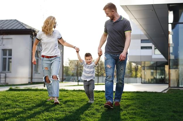Мама и папа крутят своего сына и веселятся, гуляя по улице