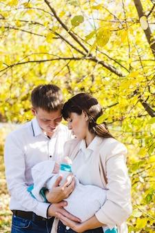 엄마와 아빠는 아기, 공원이나 숲에서 가을에 걷는 어린 소년. 노란 잎, 자연의 아름다움. 자녀와 부모 간의 의사 소통.