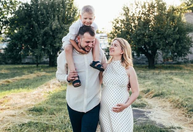 거리에서 산책을 위해 팔에 아기를 안고있는 엄마와 아빠