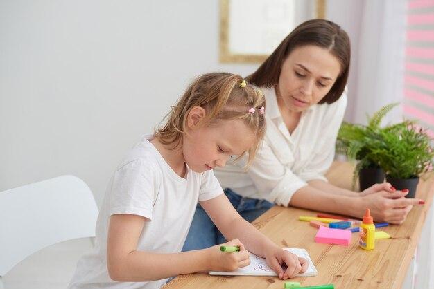 Мама и дочь делают домашнее задание. маленькая девочка задумчиво выполняет задания по математике под присмотром репетитора. концепция ухода за ребенком и помощи с домашними заданиями.
