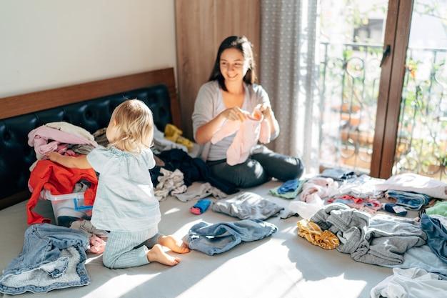 Мама и дочь складывают одежду домой
