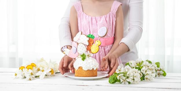 Мама и дочь держат красиво оформленный торт. концепция подготовки к семейному празднику пасхи.