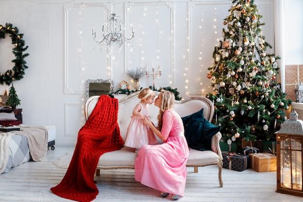 축제로 꾸며진 방에서 소파에 앉아있는 동안 엄마와 딸이 서로 키스하고 있습니다. 크리스마스 때.