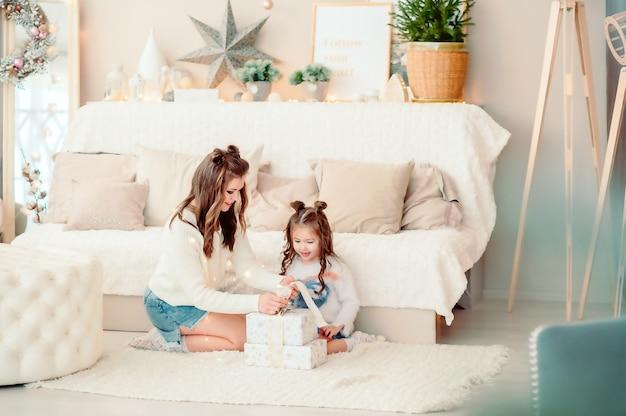 엄마와 딸은 밝고 아름다운 방에 앉아 새해 선물을 보고 있다