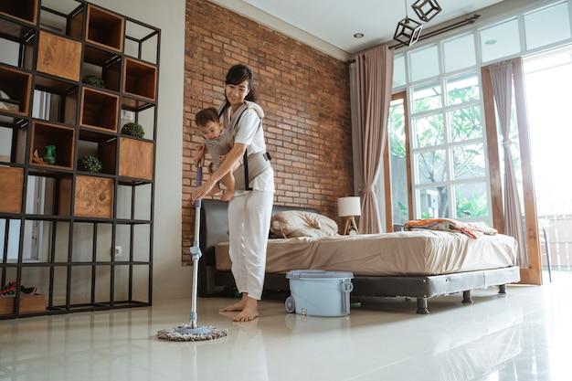 엄마와 딸이 집에서 바닥을 청소하고있다.