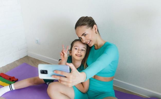 Мама и дочь фотографируются по телефону во время занятий фитнесом дома
