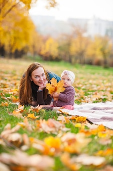 Мама и дочь играют в осенний парк.