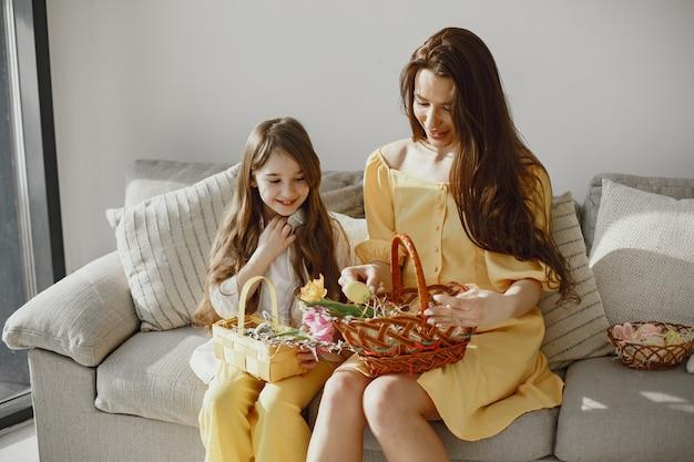 엄마와 딸은 노란색 옷을 입고 소파에 집에서 부활절을 준비하고 있습니다