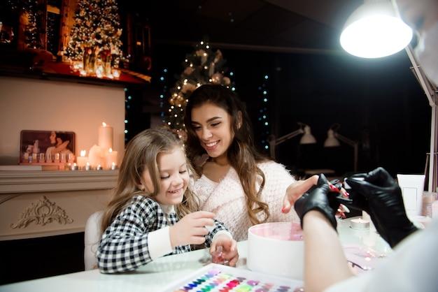 ママと娘は新年とクリスマスを祝う準備をしています。ネイルサービスのスペシャリストが美容院でマニキュアをします。