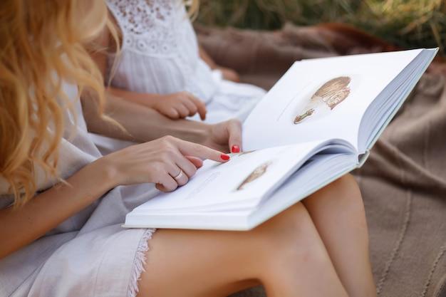ママと娘は本を読んでいます。本と手のクローズアップ。背景をぼかした写真