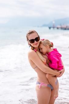 Мама и дочь отдыхают на пляже.