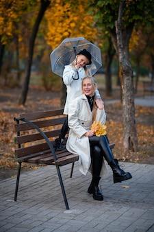 ママと娘は透明な傘の下のベンチの公園に座っています。秋の公園、家族の日