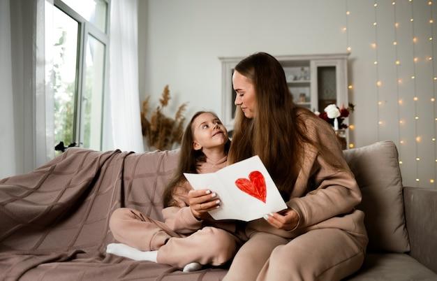 Мама и дочь сидят на диване и смотрят открытку с сердечком