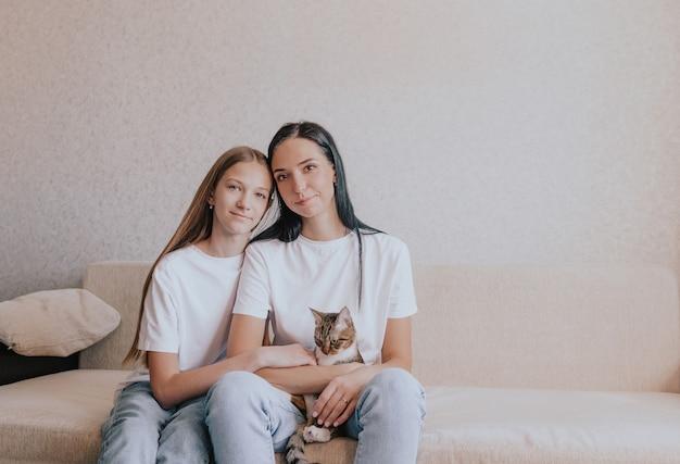 ママと娘は猫を抱いて腕を組んでソファに座っています。