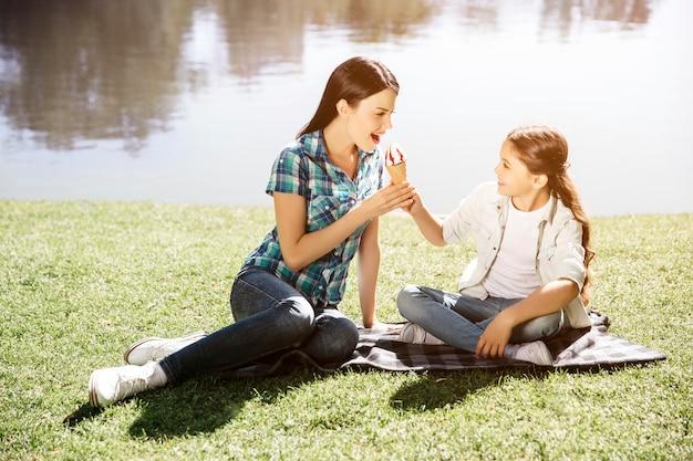 Мама и дочь сидят вместе на траве и смотрят друг на друга. они держат однажды кон мороженого вместе. женщина собирается это съесть.
