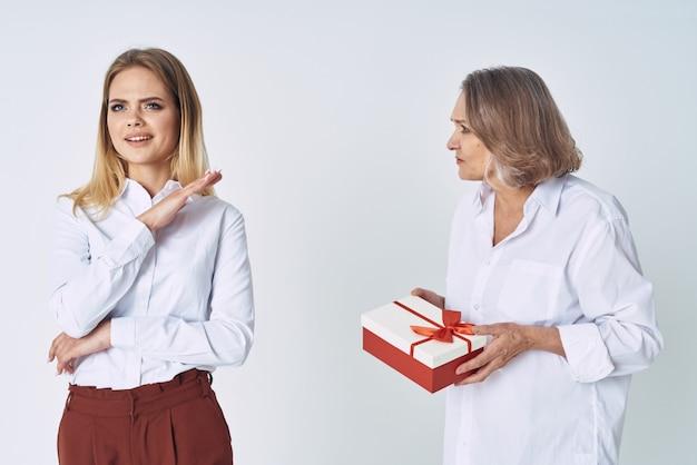 Мама и дочка стоят рядом с подарком праздничные эмоции