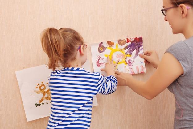 Мама и дочь пытаются повесить картину на стену