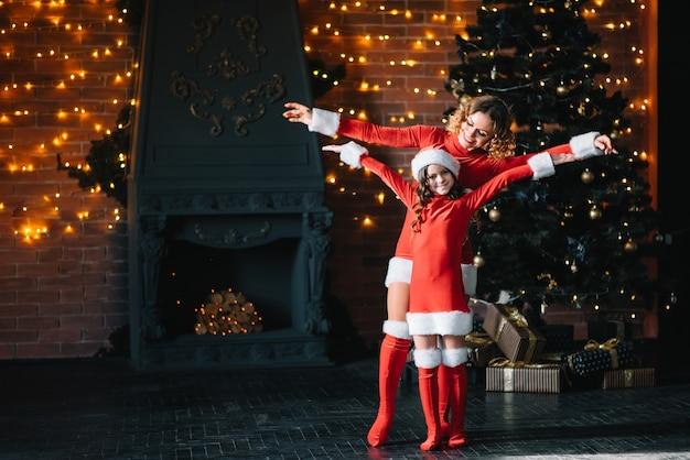 엄마와 딸은 크리스마스 트리 근처에서 새해 선물을 기다리고 있습니다.