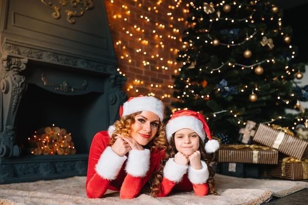 ママと娘はクリスマスツリーの近くで新年のプレゼントを待っています。