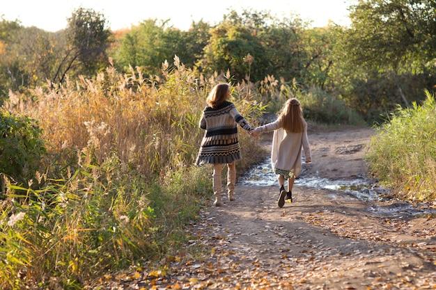 ママと娘は日没で歩いています。自然