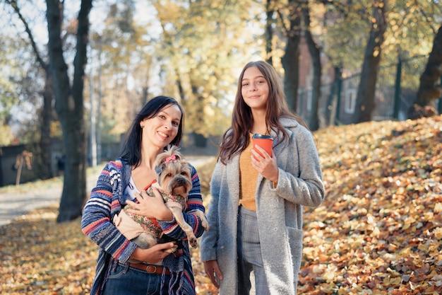 Мама и дочь гуляют в парке с маленькой собачкой