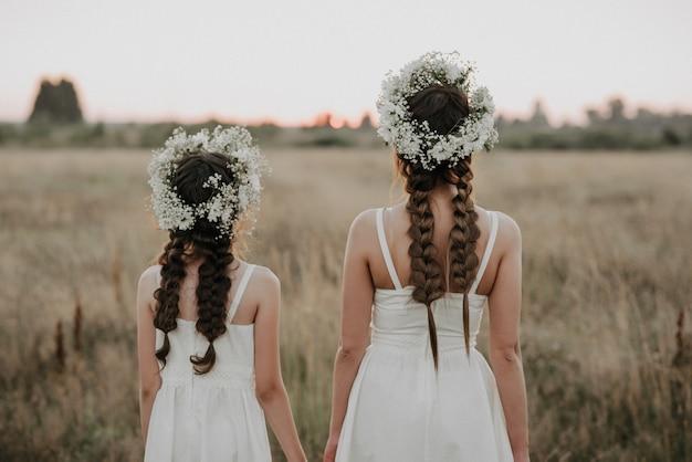 Спины мамы и дочки в белых платьях с косами и цветочными венками в стиле бохо летом