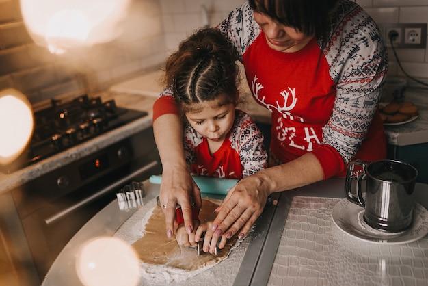 ママと娘がクリスマスクッキーを焼く
