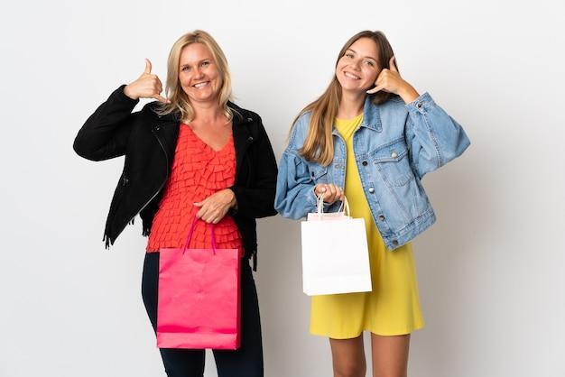 Мама и дочь покупают одежду, изолированную на белом, делая телефонный жест.