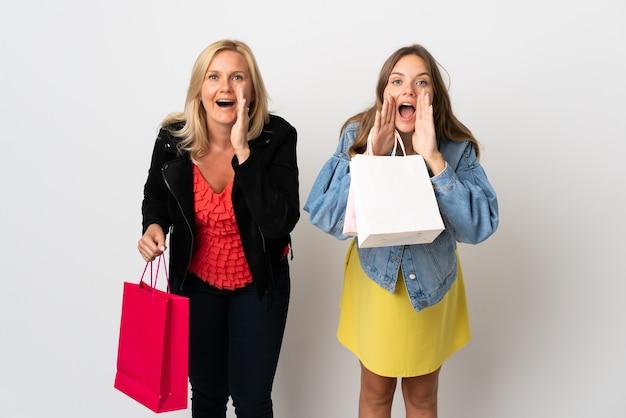 ママと娘が白い叫びと何かを発表することで孤立した服を買う