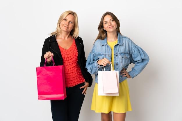 ママと娘が腰に腕を持ってポーズをとって笑顔で白い壁に隔離された服を買う