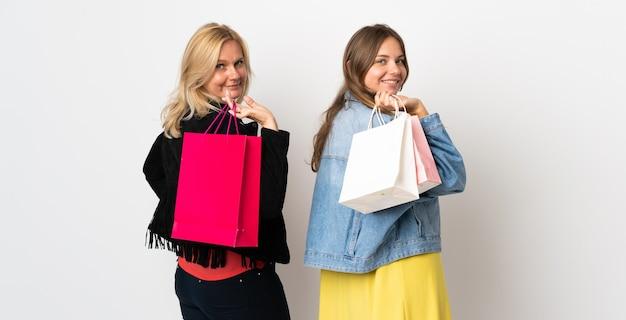 Мама и дочь покупают одежду, изолированную на белой стене