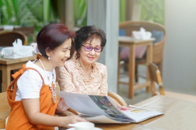 ママと娘が一緒にレストランメニューを選ぶ
