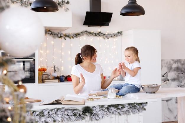 ママと娘はクリスマスの日に家でクッキーを調理します