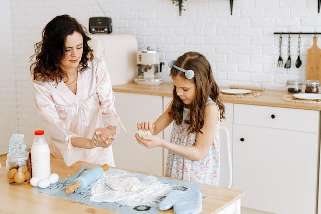 ママと娘はキッチンで一緒に料理をします。
