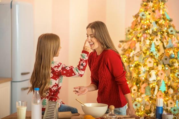 Мама и дочь вместе готовят на кухне и веселятся
