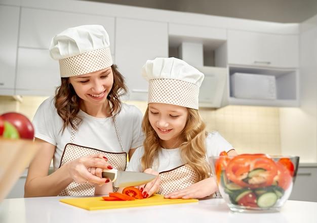 ママと娘が新鮮なサラダに野菜を切る。