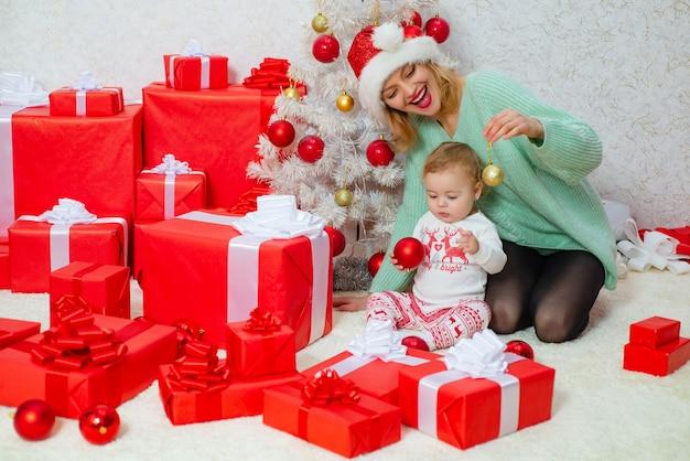 Мама и дочка украшают новогоднюю елку любящей семьей праздник рождества и вместе ...