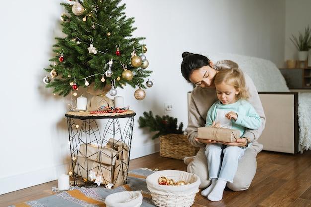엄마와 딸이 방에 크리스마스 트리를 장식합니다. 기쁜 성 탄과 새 해 복 많이 받으세요 개념입니다. 텍스트를위한 공간. 가족의 아늑한 순간.