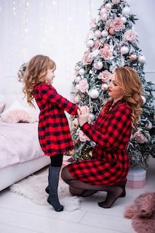 Мама и дочка украшают елку в помещении. портрет любящей семьи крупным планом.