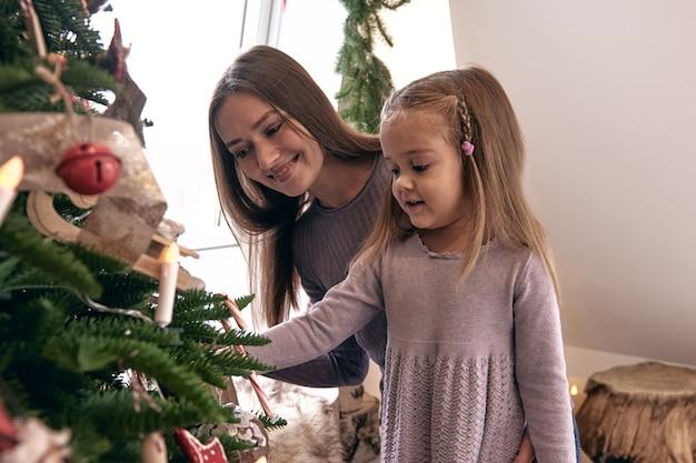 ママと娘がクリスマスツリーを飾ります。美しいholdiaydiy手作りの家の装飾の肖像画を愛する家族。キャンドルとクリスマスツリーで飾られた居心地の良い部屋とその下にプレゼント