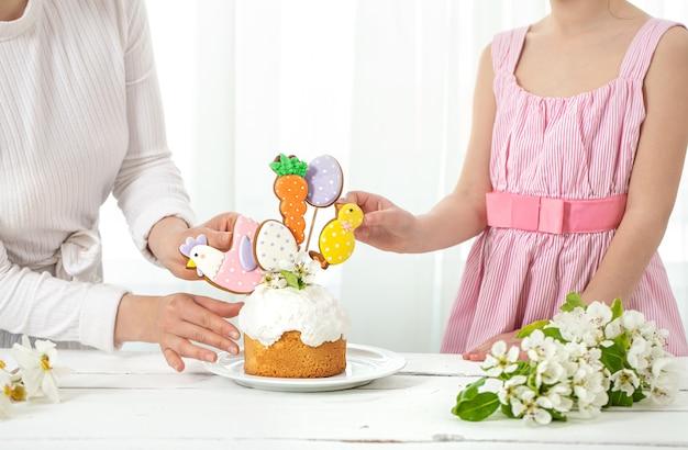 ママと娘がパクサルケーキを飾ります。家族の休日のイースターの準備の概念。