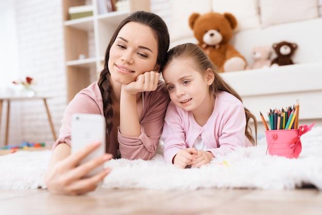 Мама и дочь делают селфи на смартфоне.