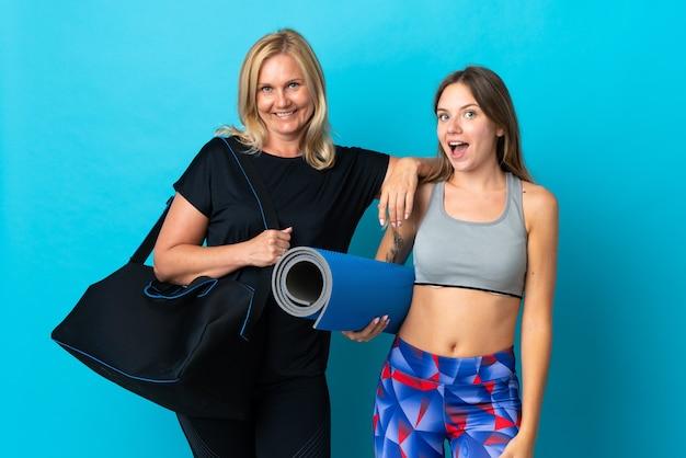 青い壁に隔離されたヨガをしているママと娘