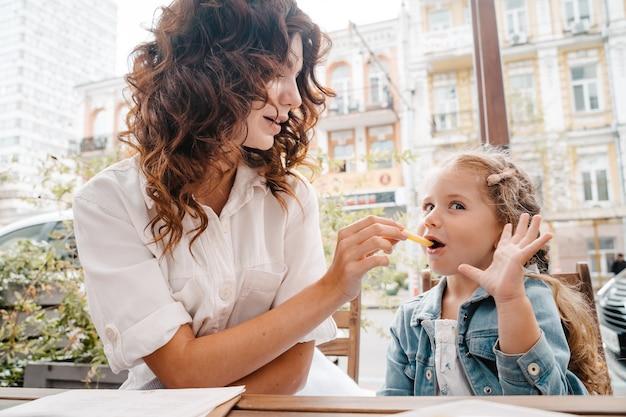 Мама и дочь едят картошку фри в летнем кафе